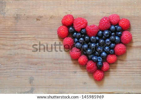Heart made from raspberry and blueberry - stock photo