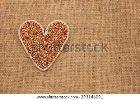 Heart made from rope with buckwheat grains  lying on sackcloth, with space for text - stock photo