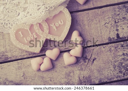 Heart made of candles and soap on wood background. - stock photo