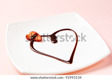 Heart made of chocolate topping and a slice of strawberry. Shallow dof, focus is on a strawberry. - stock photo