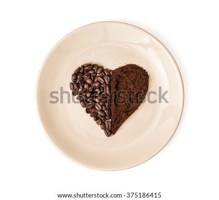 Heart made of coffee beans and ground coffee on the plate. Valentine's Day. Isolated. Symbol of love. - stock photo