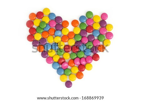 Heart made of colored smarties on a white background. - stock photo