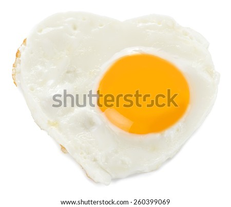 Heart made of fried egg on teflon pan isolated on white background. - stock photo