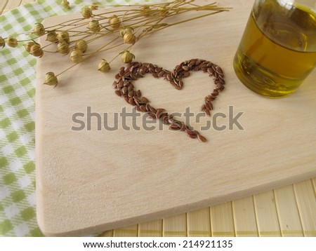 Heart made of linseed and bottle of flaxseed oil - stock photo