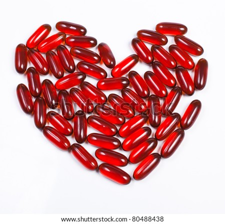 Heart made of red capsule - stock photo