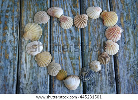 Heart made of seashells on old wooden board