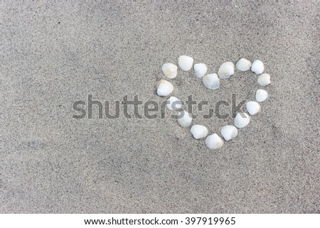 Heart made of shells on the sandy beach / heart / Shell
