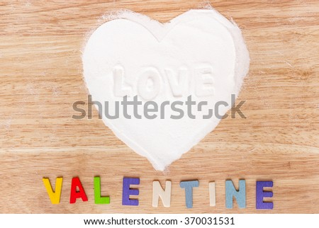 Heart made of sugar with wooden colorful word VALENTINE on wood background; Valentine's Day - stock photo