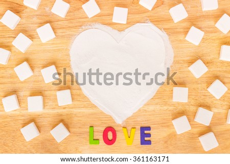 Heart made of sugar with wooden word LOVE on wood background; Valentine's Day concept - stock photo