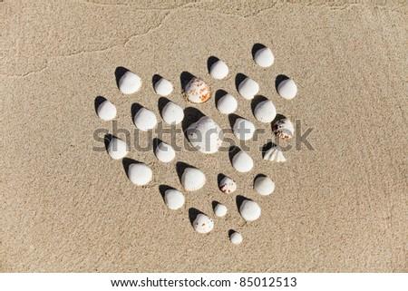 Heart made with shells. Heart shape on sand. - stock photo