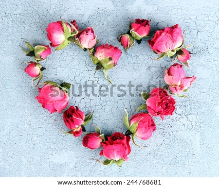 Heart of beautiful pink dried roses on old wooden background - stock photo