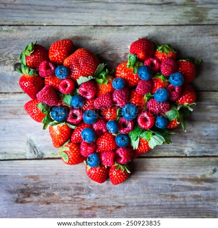 Heart of berries on wooden background - stock photo