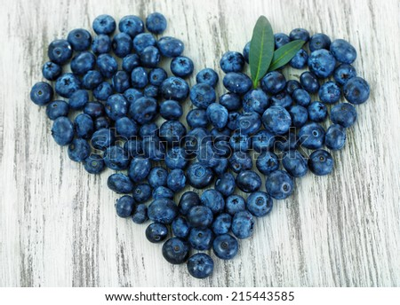 Heart of blueberries on wooden background - stock photo