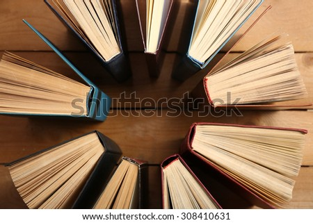 Heart of books, on wooden background - stock photo