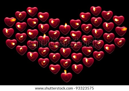 Heart of candles on a black background - stock photo