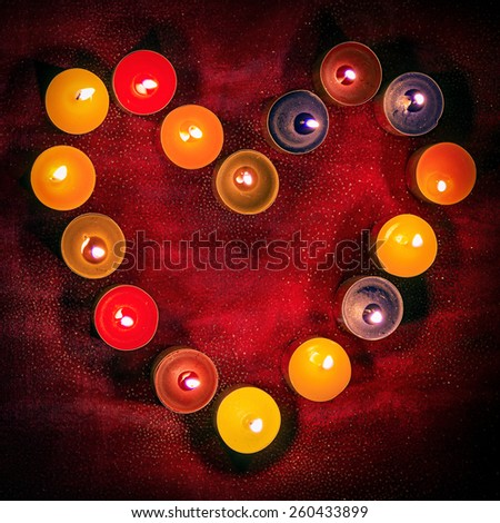 Heart of candles on red cloth