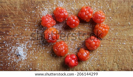 Heart of cloudberries with sugar on wooden cutting board.  - stock photo