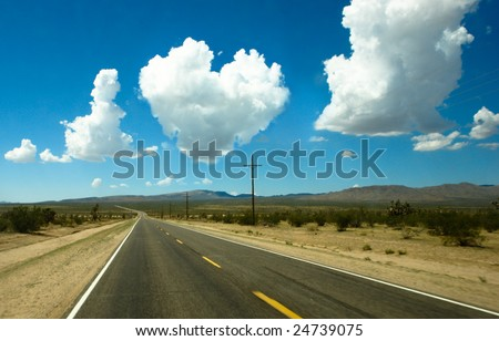 Heart of clouds in the sky above the highway in the desert - stock photo