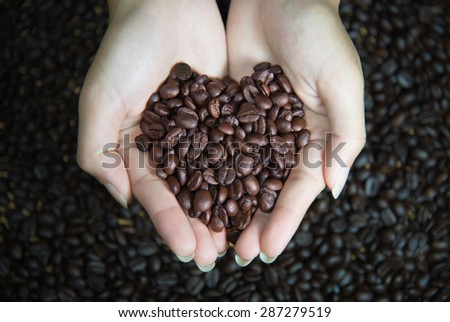 heart of cofee grains in hollow of the hand - stock photo