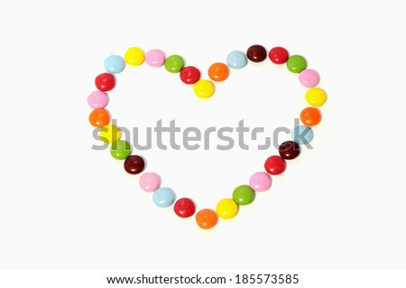 heart of colorful chocolate candy spread on white background - stock photo
