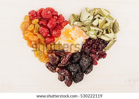 Heart of dried fruits closeup on beige wooden background. Decorative composition for Valentine's Day. Top view.