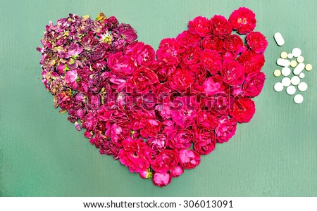 Heart of dry and fresh roses next to the pills. Modern medicine will cure a sick heart. - stock photo