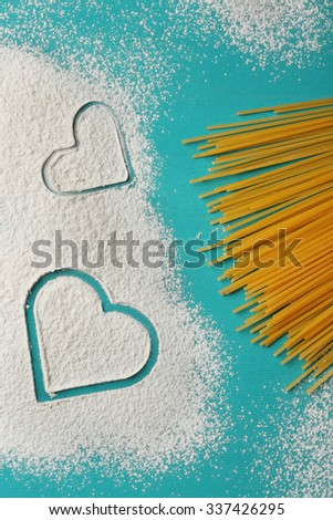 Heart of flour and pasta on blue background - stock photo