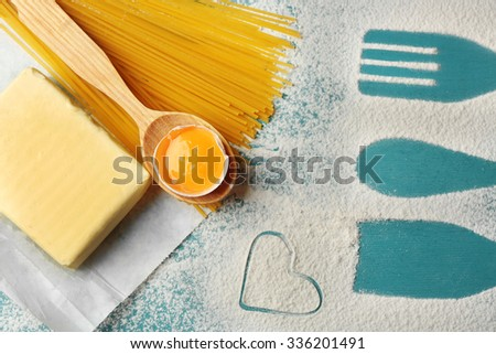 Heart of flour and pasta on color wooden background - stock photo