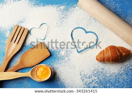 Heart of flour and  wooden kitchen utensils on blue background - stock photo