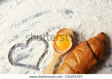 Heart of flour, croissant and wooden spoon on gray background - stock photo