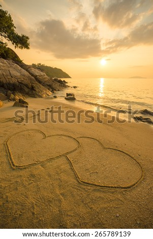 Heart of love on the beach in the sunset. - stock photo