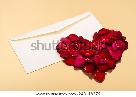Heart of red petals lying on top of an open blank envelopes on a gold background - stock photo
