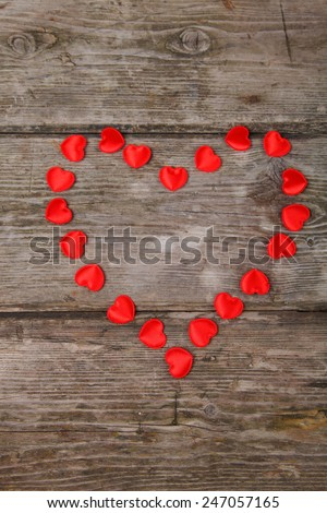 Heart of red small hearts on a wooden background. Valentines day background. - stock photo