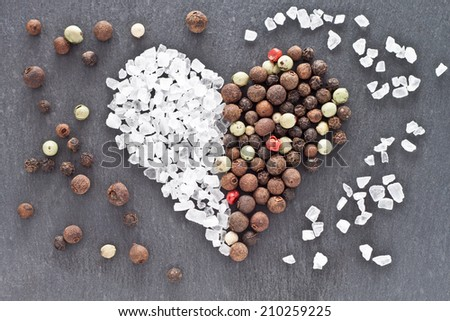 Heart of sea salt and peppercorns - stock photo