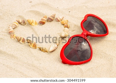 Heart of shells and red sunglasses in shape of heart lying on sand at the beach, summer time, symbol of love - stock photo