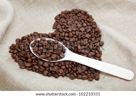 Heart of the coffee beans and wooden spoon on sacking