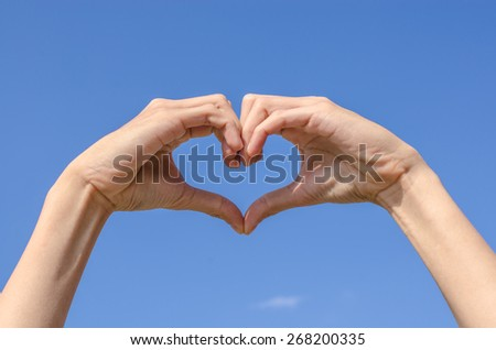 Heart of the fingers with the blue sky - stock photo