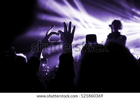 Heart of the hands, fingers. Heart hands. The gesture of love. Concert in the heart of the glare of floodlights.