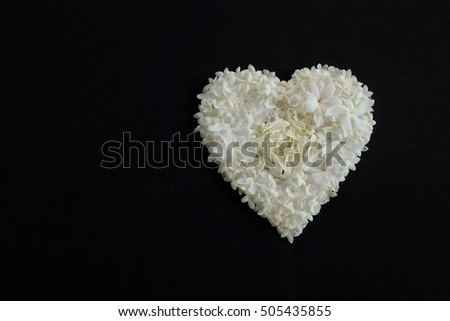 Heart of white flowers on black background
