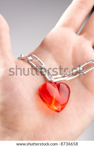 Heart on a chain wound on a palm