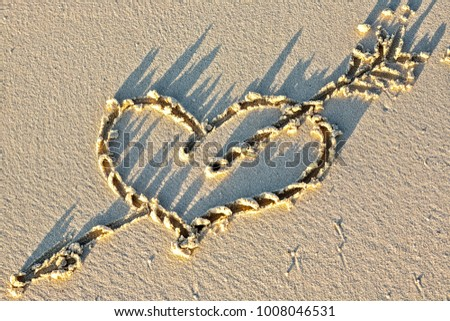 Heart on a sandy sunset beach