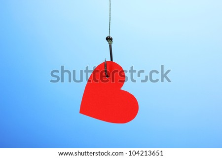 Heart on fish hook on blue background - stock photo