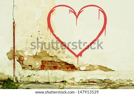 heart on old cracked wall - stock photo