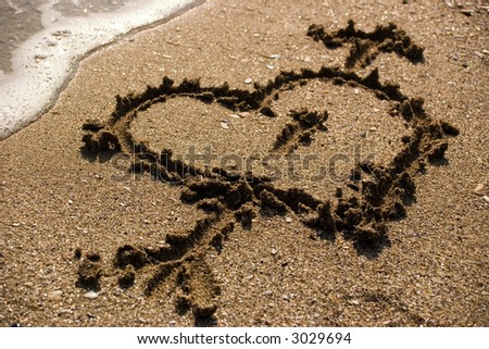heart on sand with a wave coming