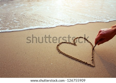 heart on the beach, hand drawing on sand - stock photo