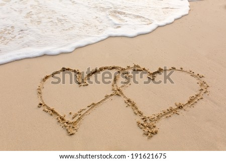 heart outline on the wet brilliance beach sand against wave - stock photo