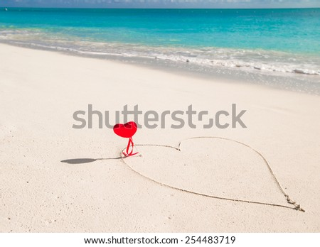 Heart painted in white sand on a tropical beach - stock photo