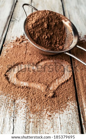heart painted on cocoa powder and sieve - stock photo