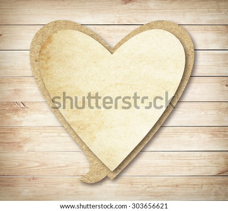 Heart paper speech bubble with shadow on brown wooden wall - stock photo