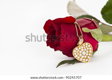 Heart pendant with diamond and red rose on white background